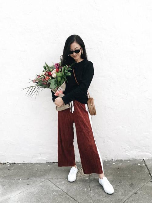 Девушка в широких брюках, черном джемпере и белых кроссовках