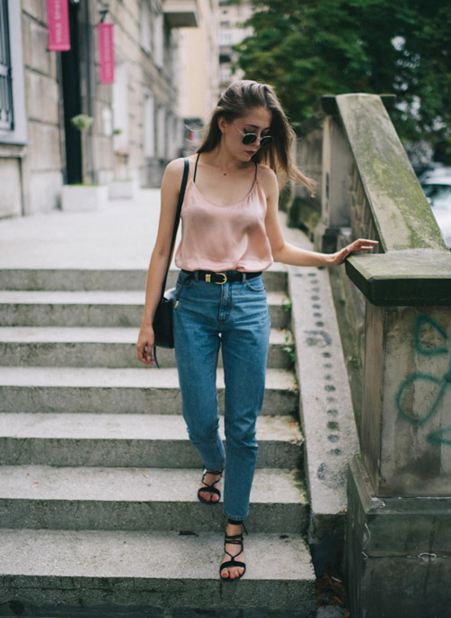 Девушка в синих джинсах, босоножках и нежно-розовом топе