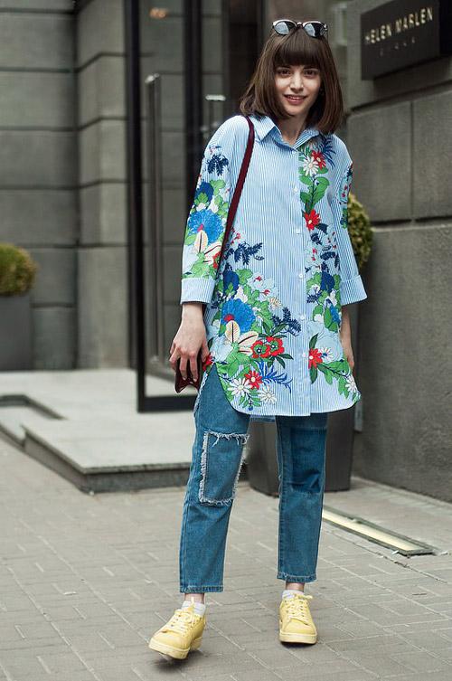 Девушка в свободных джинсах с заплатами и длинной полосатой рубашке с принтом