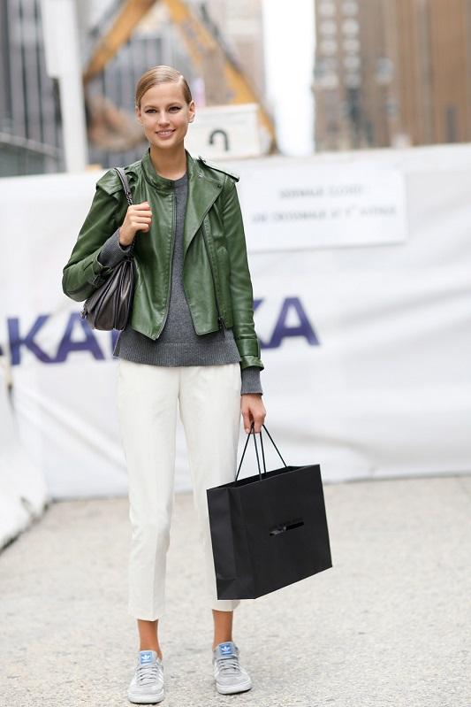 Модель в белых брюках капри, серой кофточке и зеленой кусухе