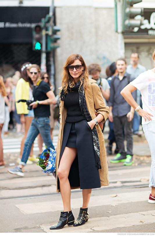 Модная девушка в темной юбке, топе и светлом пальто с шарфиком на шее
