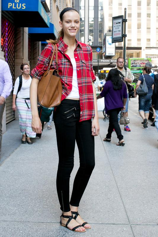 Девушка в черных брюках, белом топе и красной рубахе в клетку