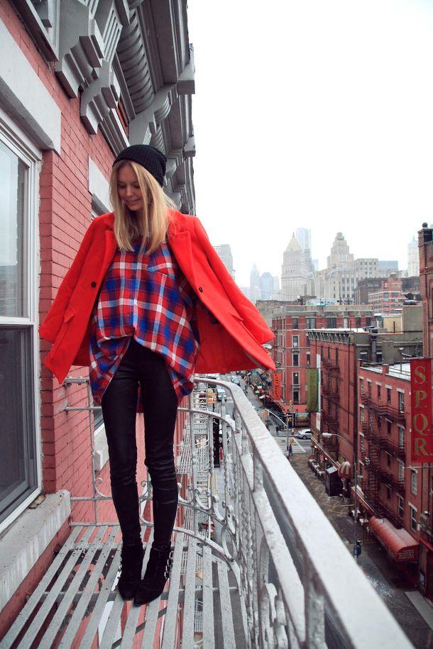 Модель с черных брюках, широкой рубахе в клетку и красном пальто