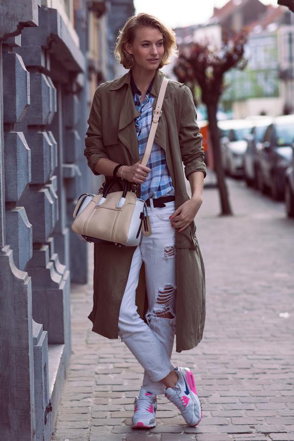 Модель в белых рваных джинсах, рубахе в клетку и длинном коричневом плаще