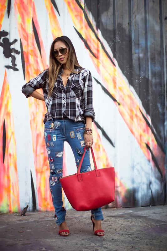 Модель в джинсах с наклейками т коричнево-серой рубахе в клетку