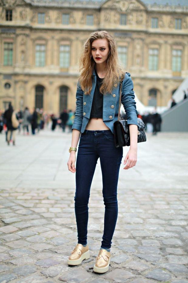 Модель в темно-синих джинсах, голубом пиджаке и золотых криперах на белой платформе