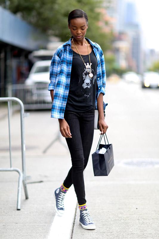 Модель в узких брюках, черной футболке и голубой рубахе в клетку