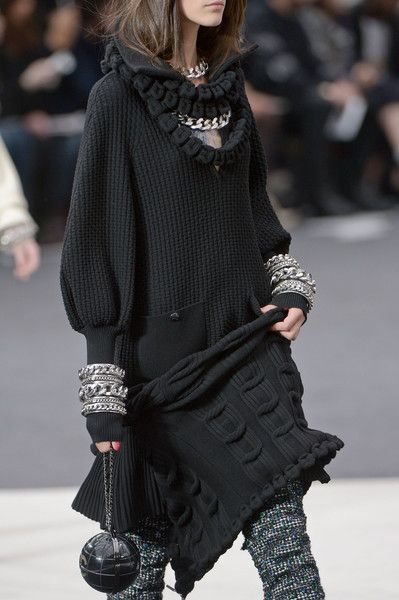 Девушка в черном вязанном платье свитер, с аксессуарами в виде цепей