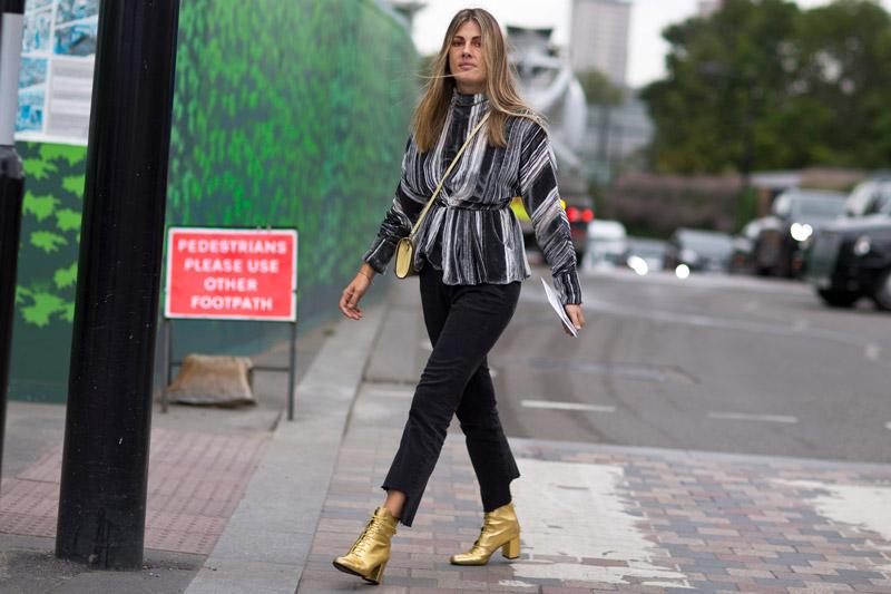 Девушка в черных брюках, черно-белой кофте и золотых ботинках