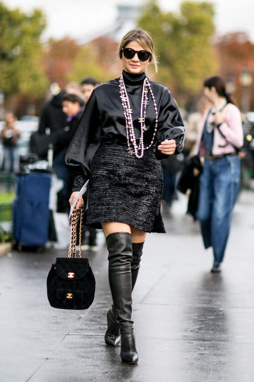 Девушка в черных сапогах выше колен, черной юбке и блузе