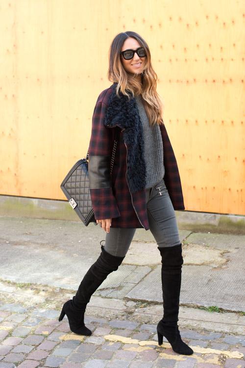 Девушка в черных сапогах выше колен, серые джинсы и свитер, пальто в клетку