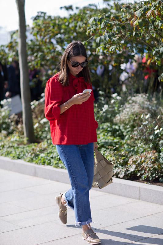 Девушка в красной блузе с бантом и широких джинсах, бежевые туфли и сумка