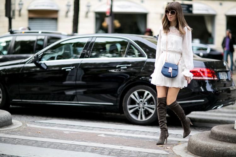 Девушка в сапогах выше колен, белое воздушное платье и маленькая синяя сумочка