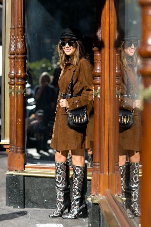 Девушка в сапогах выше колен, коричневый плащ и черная кепка