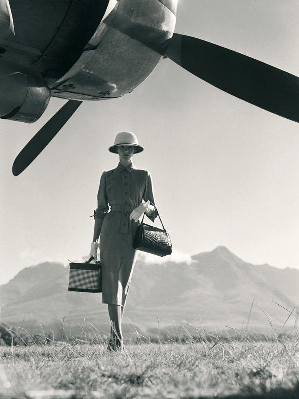 Девушка в строгом платье стоит посреди поля