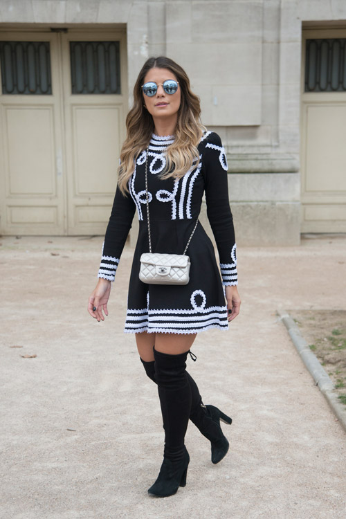 Модель с сапогах выше колен и черно-белом платье, маленькая белая сумочка