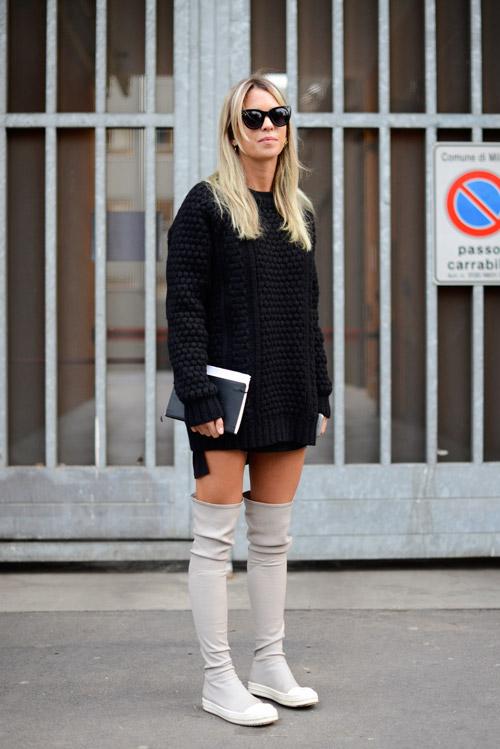 Модель с сапогах выше колен молочного цвета и черном саитере с крупной вязкой