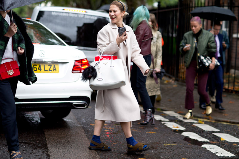 Модель в белом пальто, синие ности, сланцы и белая сумка