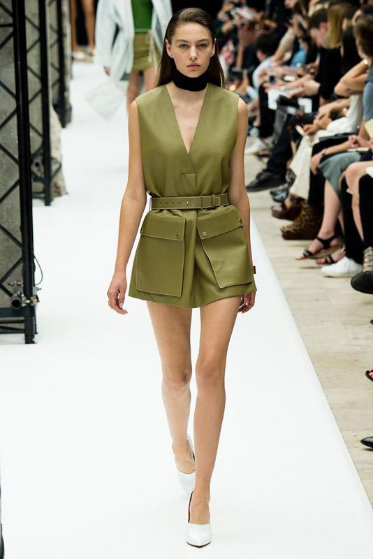 Модель в болотном платье и белых туфлях