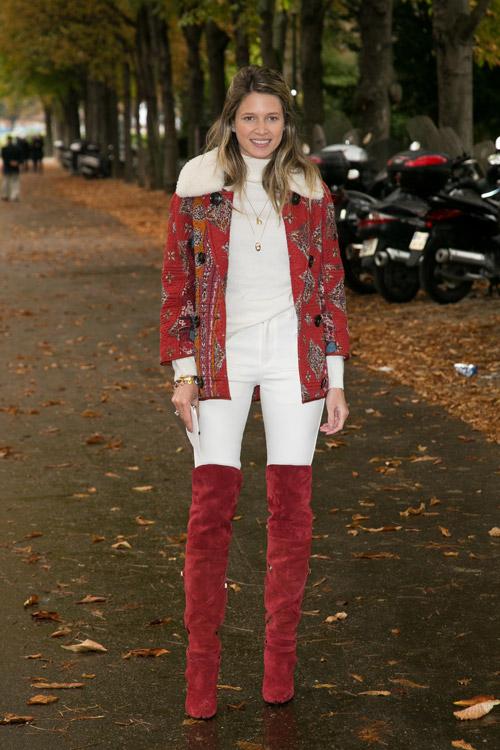 Модель в бордовых сапогах выше колен, белых брюках и кофте, красная куртка с принтом