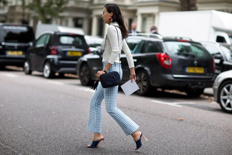 Модель в брюках в бело-голубую клетку и светлой водолазке