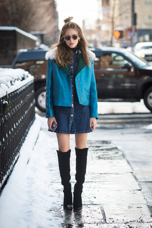 Модель в черных сапогах выше колен, джинсовом платье и голубой куртке