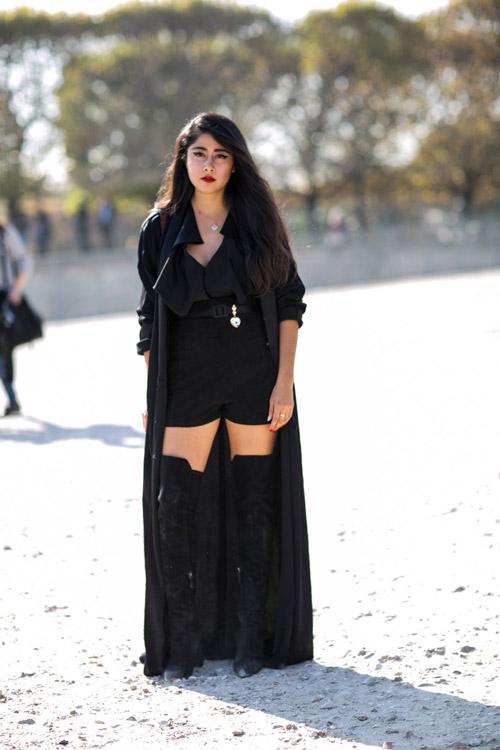 Модель в черных сапогах выше колен, короткие шорты, блуза и длинный плащ