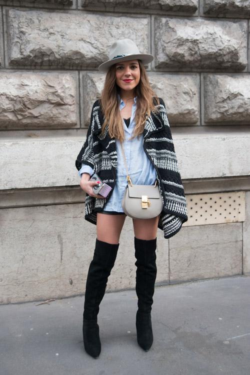 Модель в черных сапогах выше колен, мини шортах, черно-белой накидке и шляпе