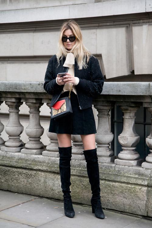 Модель в черных сапогах выше колен, мини юбка и теплая кофта на замке