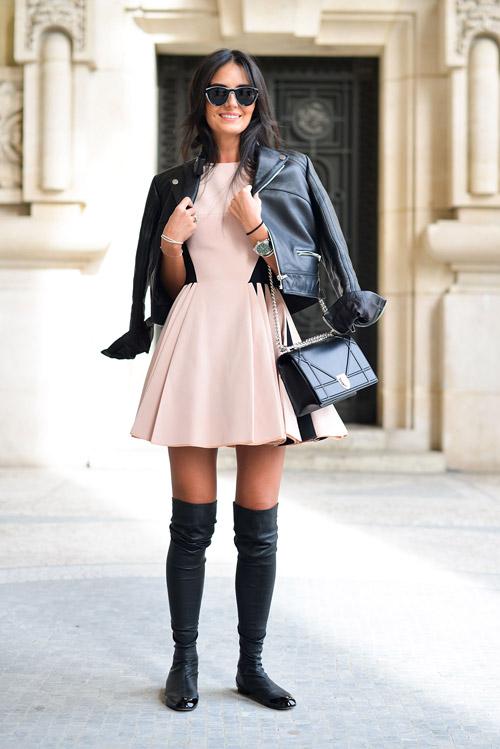 Модель в черных сапогах выше колен на плоской подошвн, светлое мини платье и куртка косуха