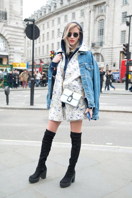 Модель в черных сапогах выше колен на высокой платформе, синей джинсовке и маленькая белая сумочка