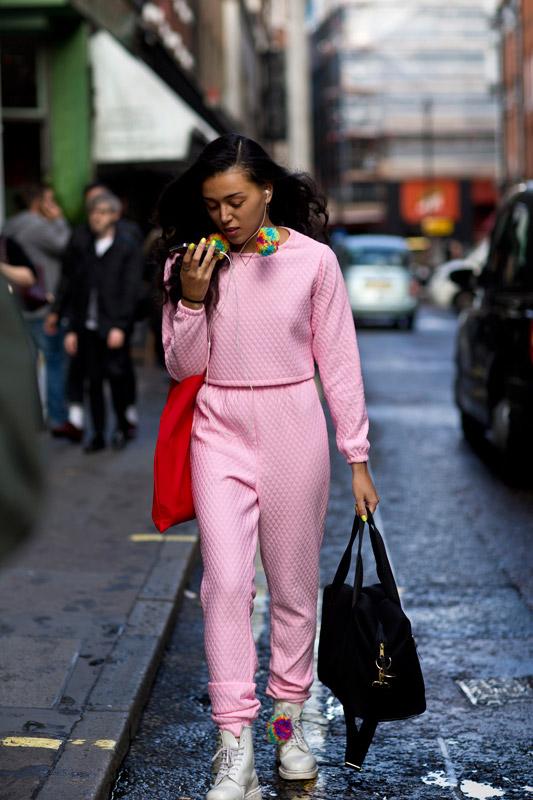 Модель в розовом комплекте со штанами и кофтой в спортивном стиле, черная спортивная сумка