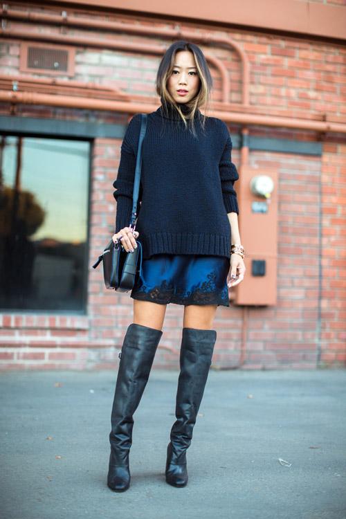 Модель в сапогах выше колен, миниюбке и черный свитер