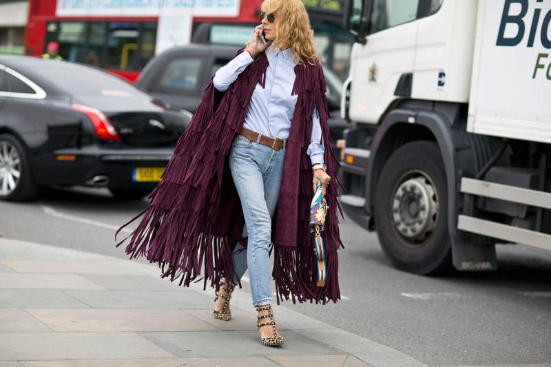 Модель в светлых джинсах, белой рубахе и фиолетовом плаще с бахромой