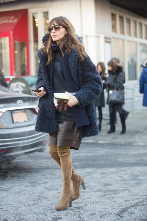 Осенний образ, модель в коричневых сапогах выше колен, кожаной юбке по коленго и темно синем пальто