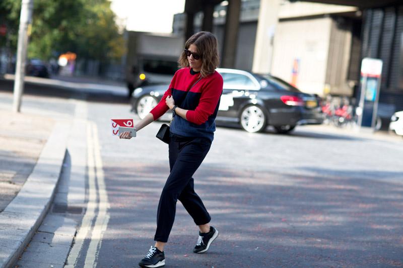 Спортивный образ, модель в черных брюках и черно-красном свиншоте