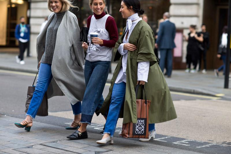 Три девушки в свободных джинсах с рваным краем и плащах, осенние образы