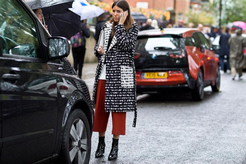 модель с красный бриджах со стрелками и черно-белом пальто