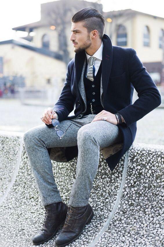 мужчина в черном пальто и серых штанах