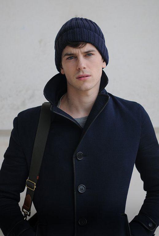 мужчина в черном пальто и синей шапке