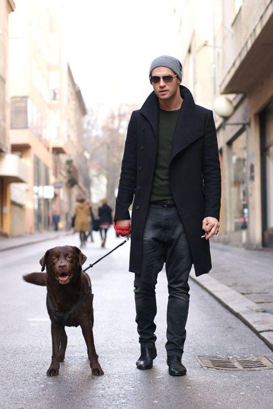 мужчина в черном пальто с собакой