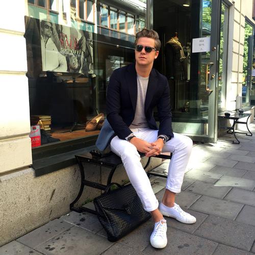 мужчина в черном пиджаке и белых брюках