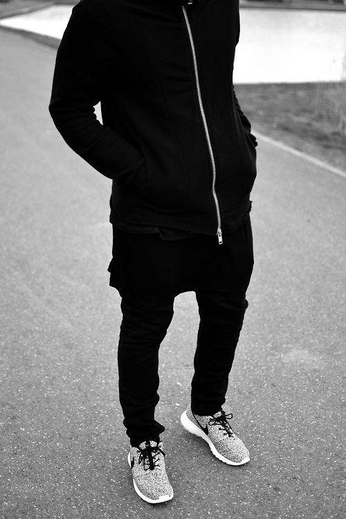 мужчина в черной толстовке и серых кроссовках
