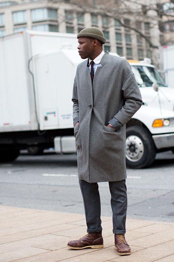 мужчина в сером пальто и болотной шапке