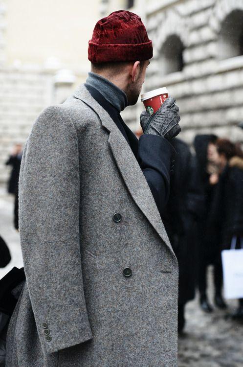 мужчина в сером пальто и красной шапке