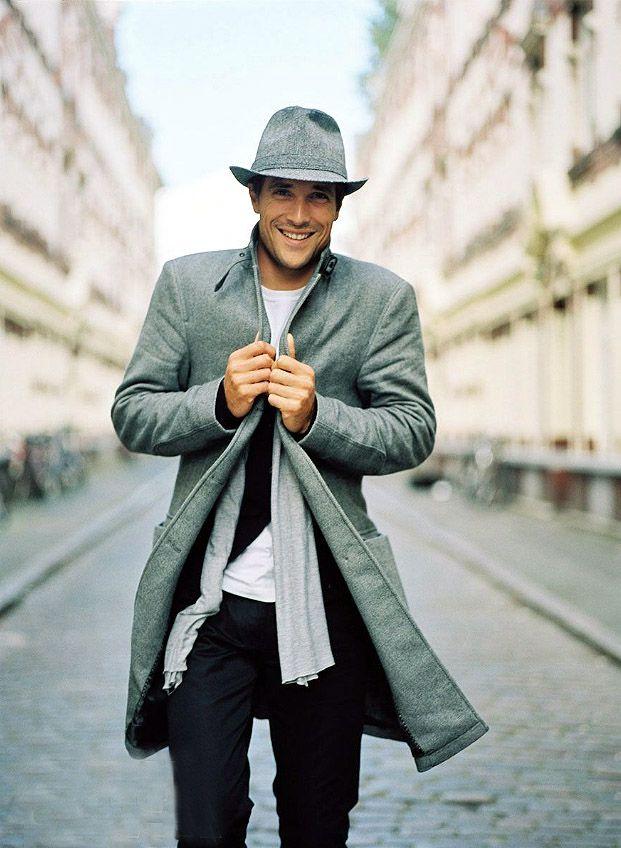 мужчина в сером пальто и шляпе