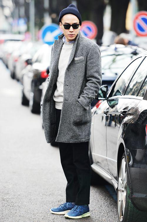 мужчина в сером пальто, кроссовках и шапке