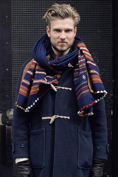 мужчина в синем пальто и с этническим шарфом