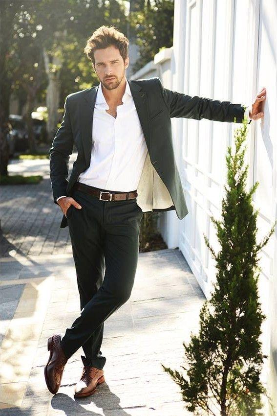 мужчинав черном пиджаке, черных брюках и белой рубашке