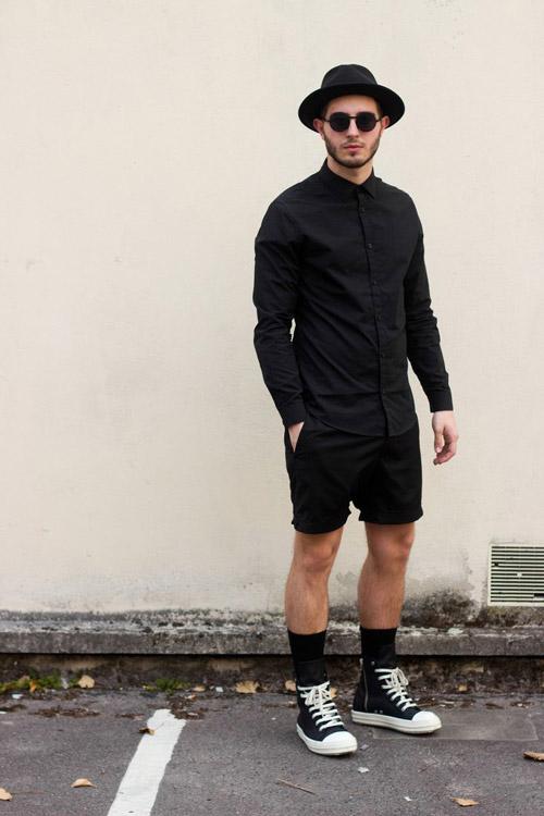 мужчинав черных кедах и черных шортах